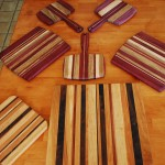 A beautiful array of cutting boards - notice some have handles, others have a curved edge, and others are rectangular