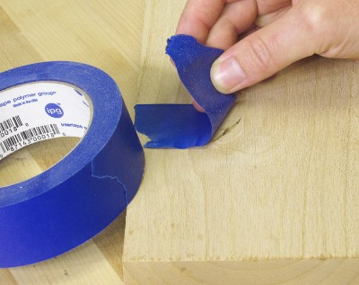 If the knots or cracks go all the way through your board, flip it over and cover the backside of the void with masking tape. This helps prevent a nasty mess leaking through, or worse your board getting glued to your workbench.